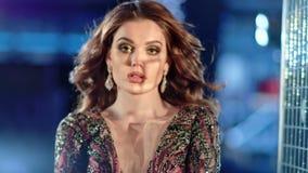 Luxe jonge vrouw die diamantoorringen en het glanzende kleding stellen dragen bij de achtergrond van bokehlichten stock footage