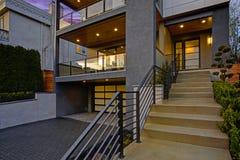 Luxe modern huis buiten bij zonsondergang stock fotografie