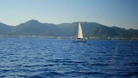 Luxe mooi jacht in blauwe overzees op bergachtergrond, Middellandse Zee stock video