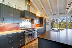 Luxe mooie donkere moderne keuken met gewelfd houten plafond stock foto's