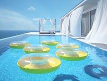Luxe zwembad met swimmrings het 3d teruggeven Stock Foto's