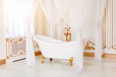 Luxebadkamers in lichte kleuren met gouden meubilairdetails en luifel Elegant klassiek binnenland stock afbeelding