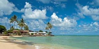 Luxehuis op onaangeroerd zandig strand met palmenbomen en azuurblauw Stock Foto's