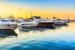 Luxejachten in zeehaven bij zonsondergang worden gedokt die Marien parkeren van moderne motorboten en blauw water Stock Afbeelding