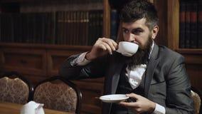 Luxelevensstijl, succes, elegantie, het concept van de theetijd De aristocraat zit in luxebinnenland en drinkt thee of koffie stock footage