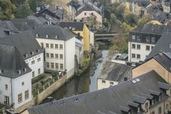 Luxembourg city details. Top view with bridge across Alzette river. In downtown Luxembourg and details of traditional vintage houses in dark November day Royalty Free Stock Images