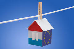 Luxembourg and EU flag on paper house. Concept - Luxembourg and EU flag painted on a paper house hanging on a rope Stock Photos