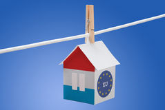 Luxembourg and EU flag on paper house. Concept - Luxembourg and EU flag painted on a paper house hanging on a rope Royalty Free Stock Photos