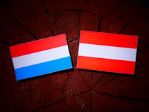 Luxembourg flag with Austrian flag on a tree stump. Luxembourg flag with Austrian flag on a tree stump Royalty Free Stock Photos