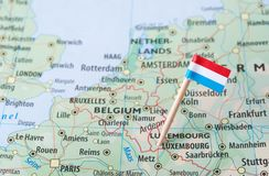 Luxembourg flag on a country map. Paper flag pin of Luxembourg on a map. Officially the Grand Duchy of Luxembourg, it is a landlocked country in Western Europe Royalty Free Stock Image