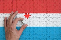 Luxembourg flag is depicted on a puzzle, which the man`s hand completes to fold.  vector illustration