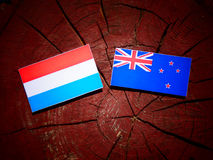 Luxembourg flag with New Zealand flag on a tree stump isolated. Luxembourg flag with New Zealand flag on a tree stump Royalty Free Stock Images