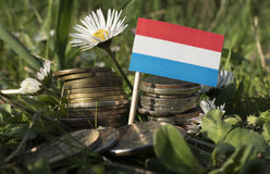 Luxembourg flag with stack of money coins with grass stock image