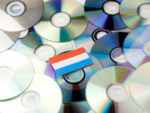 Luxembourg flag on top of CD and DVD pile isolated on white. Luxembourg flag on top of CD and DVD pile isolated Royalty Free Stock Photo
