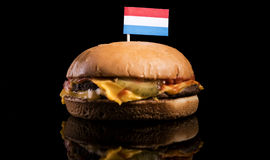 Luxembourg flag on top of hamburger isolated on black Royalty Free Stock Images