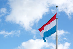 Luxembourg flag is waving in front of blue sky and puffy clouds Stock Images