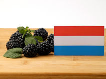 Luxembourg flag on a wooden panel with blackberries isolated on. A white background Stock Photo