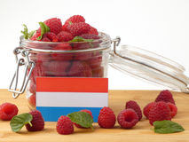 Luxembourg flag on a wooden panel with raspberries isolated on a. White background Stock Image