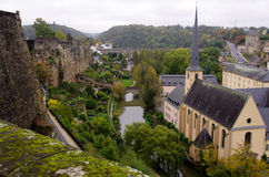 Luxembourg Fortess Ruins and Catherdral. The river Alzette winding the old walls of the fortress of Luxembourg with a cathedral on the lower bank and old stone stock images
