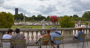 Luxembourg garden, Paris. PARIS - AUG 12: Visitors sit in Luxembourg garden in Paris, France on August 12, 2016. The garden was created in 1612 royalty free stock images