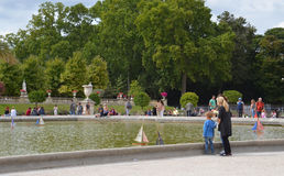 Luxembourg garden, Paris. PARIS - AUG 12: Visitors watch boats on the fountain in Luxembourg garden in Paris, France on August 12, 2016. The garden was created stock images