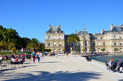 Luxembourg Garden in Paris. People enjoy sunny day in the Luxembourg Garden in Paris. Luxembourg Palace is the official residence of the French Senate stock image