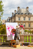 Luxembourg Gardens Artist. An unidentified female artist painting in the Luxembourg Gardens in Paris, France, with the Luxembourg Palace in the background Royalty Free Stock Images