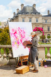 Luxembourg Gardens Artist. An unidentified female artist painting in the Luxembourg Gardens in Paris, France, with the Luxembourg Palace in the background Stock Images