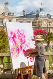 Luxembourg Gardens Artist. An unidentified female artist painting in the Luxembourg Gardens in Paris, France, with the Luxembourg Palace in the background Royalty Free Stock Photos