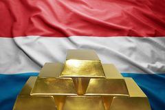 Luxembourg gold reserves. Shining golden bullions on the luxembourg flag background Stock Photo