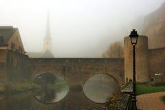 Luxembourg överbryggar över den Alzette floden i dimman Arkivfoto