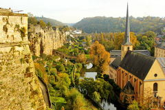 Luxembourg: Grund, abbey and the ancient fortifications of the city. View of Luxembourg lower part called Grund and of the monastery in a beautiful sunny day of Stock Photos