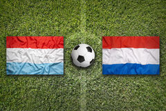 Luxembourg vs. Netherlands flags on soccer field Stock Image