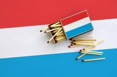 Luxemburgo embandeira é mostrado em uma caixa de fósforos aberta, de que diversos fósforos caem e mentiras em uma grande bandeira imagens de stock royalty free