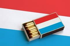 Luxemburgo embandeira é mostrado em uma caixa de fósforos aberta, que seja enchida com os fósforos e se encontre em uma grande ba imagem de stock