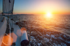 Luxery sailing yacht glides through the waves during a wonderful sunset. Travel. Luxery sailing yacht glides through the waves during a wonderful sunset Stock Photo