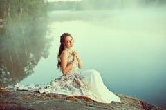 Luxevrouw in een bos in een lange uitstekende kleding dichtbij het meer Royalty-vrije Stock Afbeeldingen