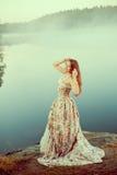Luxevrouw in een bos in een lange uitstekende kleding dichtbij het meer Stock Foto's