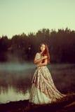 Luxevrouw in een bos in een lange uitstekende kleding dichtbij het meer Stock Foto