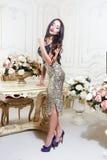 Luxevrouw met lang donkerbruin krullend haar en rode lippen in gouden kleding en hoge hielen die in studio dichtbij lijst stellen Royalty-vrije Stock Fotografie