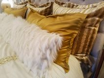 Luxiourous gold and fur pillow shams on bed propped against quilted beadstead royalty free stock photography