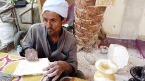 Luxor, Ägypten - 2019-05-01 - Mann schnitzt Muster auf Clay Tablet For Decoration stock video footage
