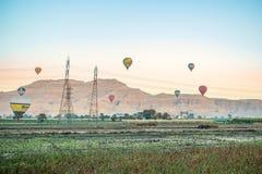 12/11/2018 Luxor, Egipt gorące powietrze balony wzrasta przy wschód słońca nad zieloną oazą w pustyni obraz stock