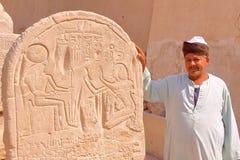 LUXOR, EGIPTO - 4 DE NOVIEMBRE DE 2011: Un hombre egipcio que presenta delante de jeroglíficos en el templo de Seti I imagen de archivo