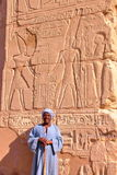 LUXOR, EGYPT - NOVEMBER 2, 2011: Portrait of a guard in front of hieroglyphs in Karnak temple stock images