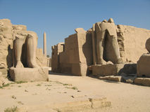 Luxor temple. In Egypt with two ruined statues in the foreground and the obelisk behind stock photo