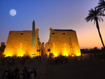 Luxor temple at night. First pylon, obelisk and colossus at Luxor temple. Thebes. Egypt series. Unrecognizable people Stock Image