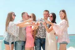 Luxueus vakantieconcept Een groep gelukkige vrienden op een blauwe overzeese achtergrond Volwassenen die in de zonglazen en zomer royalty-vrije stock foto's