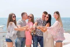 Luxueus vakantieconcept Een groep gelukkige vrienden op een blauwe overzeese achtergrond Volwassenen die in de zonglazen en zomer stock afbeeldingen