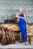 Luxueuze blondevrouw in een witte kleding met een pekingese hond royalty-vrije stock fotografie